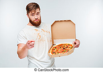 Confident bearded man holding pizza box and pointing at camera
