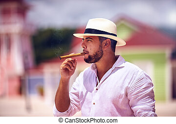 confident bearded man smoking cigar on caribbean street