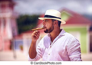 confident bearded man smoking cigar on caribbean street