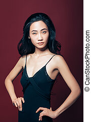 Confident beautiful asian girl in black dress, hands on hips