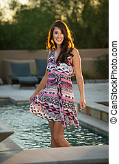Beautiful brunette fashion model standing on the edge of a pool posing outdoors.