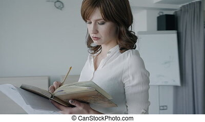 Confident beautiful businesswoman writing in notebook standing in modern office.