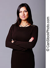 Confident beautiful woman standing with arms folded