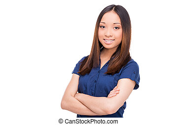 Confident beauty. Beautiful young Asian woman looking at camera and keeping arms crossed while standing isolated on white