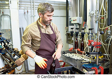 Confident beer factory worker putting bottles in box -...