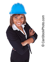 Confident Black African American woman architect smiling with folded arms, isolated on white background