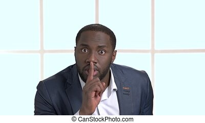 Confident black businessman showing silence gesture....