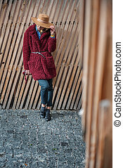 Confident blond lady standing near wood palisade