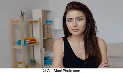 Confident brunette businesswoman in black top with folded arms in office