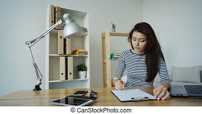Confident brunette businesswoman in striped blouse and glasses taking note in a notepad at office
