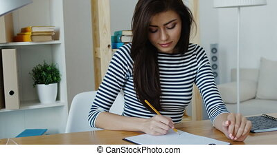 Confident brunette businesswoman taking note in a notepad at office, close-up