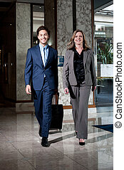 Confident business colleagues entering hotel lobby with lugguage