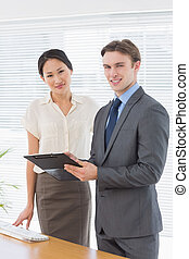 Confident business colleagues with clipboard at office