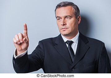 Confident business expert. Confident mature man in formalwear looking at camera and keeping arms crossed while standing against grey background
