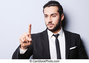 Confident business expert. Confident young man in formalwear pointing and looking at his finger while standing against grey background
