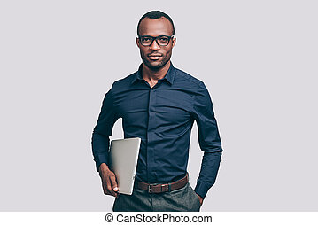 Confident business expert. Handsome young African man carrying laptop and looking at camera while standing against grey background