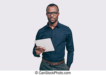 Confident business expert. Handsome young African man holding digital tablet and looking at camera while standing against grey background