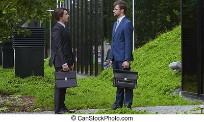 Confident business men in front of office building....