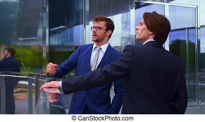 Confident business men talking in front of modern office...