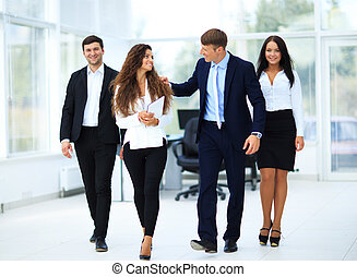 Confident business partners walking down in office building...