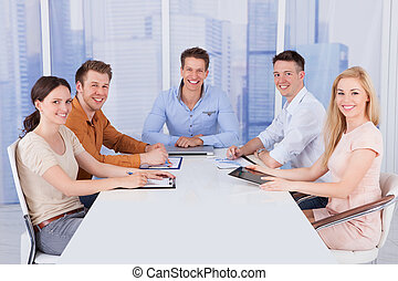 Confident Business People At Conference Table In Office