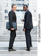 Confident business people. Full length of two cheerful business men looking over shoulder and smiling while standing on staircase