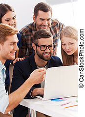 Confident business team. Group of cheerful business people in smart casual wear looking at the laptop together and smiling