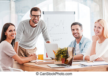Confident business team. Group of cheerful business people in smart casual wear sitting at the desk together and smiling