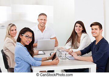 Confident Business Team Sitting At Desk