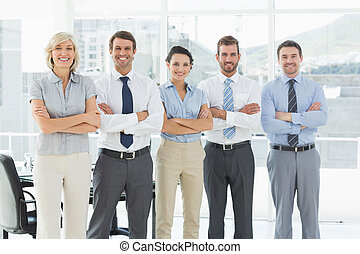 Confident business team with arms crossed in office