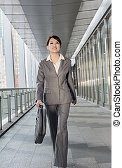 Confident business woman holding briefcase and walking