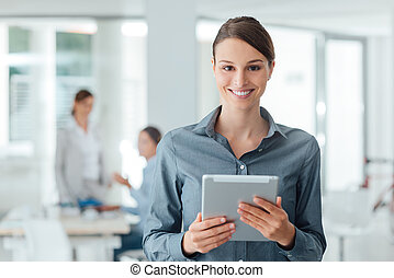 Confident business woman using a touch screen tablet