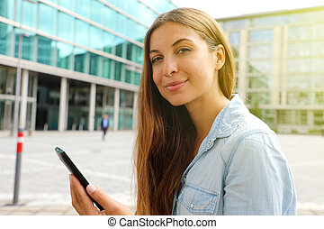 Confident business woman using her smart phone sitting outdoor