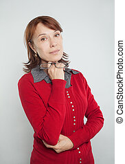 Confident business woman with glasses. Portrait of friendly mature woman in red cardigan