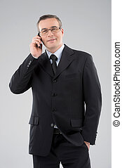 Confident businessman. Confident middle-age man in formalwear talking on the mobile phone isolated on grey