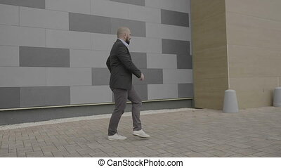 Confident businessman dancing freestye dance on his way to...