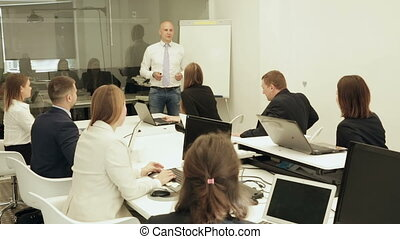 Confident successful businessman discussing new business project with members of his team