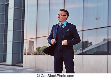 e84d3d3ad Confident businessman dressed in an elegant suit looking away and button up  his jacket while standing