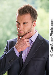 Confident businessman. Handsome young man in formalwear looking away and holding hand on chin
