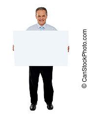 Confident businessman holding blank billboard