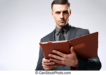 Confident businessman holding tablet computer over gray background