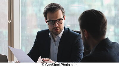 Confident businessman in eyeglasses discussing contract ...