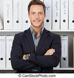 Confident Businessman In Front Of Folders