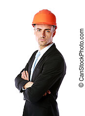 Confident businessman in helmet standing with arms folded...