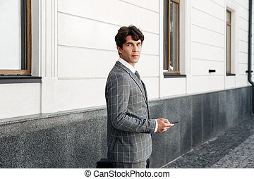 Confident businessman in suit holding car keys while standing outdoors