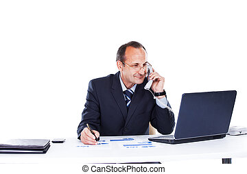Confident businessman in the workplace in the office of a laptop talking on the phone