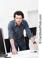 Confident businessman leaning on his desk