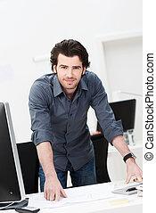 Confident businessman leaning on his desk - Confident ...