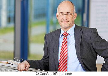 Confident Businessman Leaning On Podium