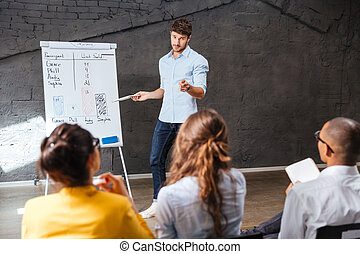 Confident businessman making presentation using whiteboard in office